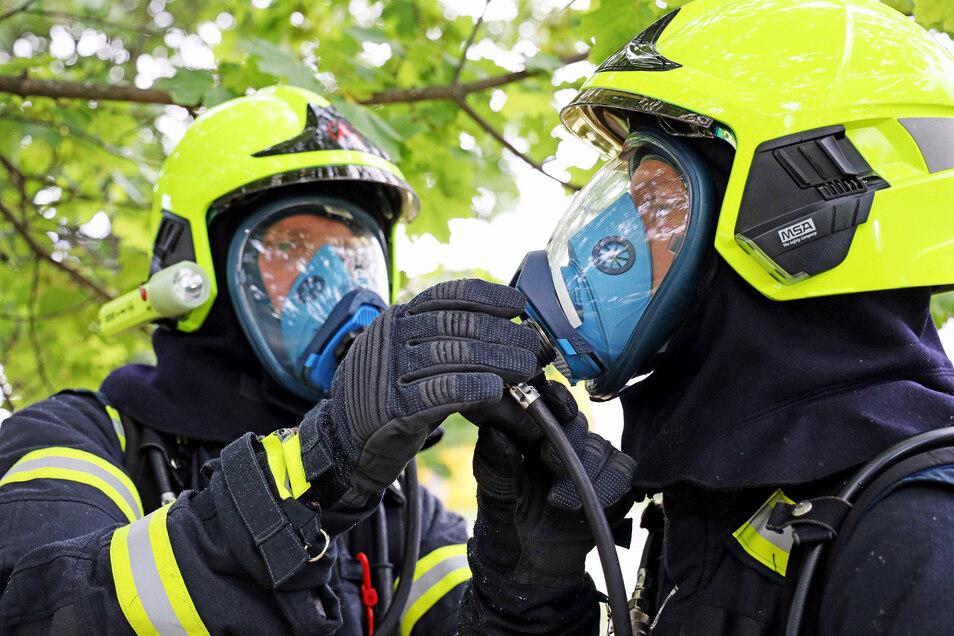Die Glaubitzer Feuerwehrleute helfen sich beim Anschließen des Sauerstoffschlauchs an die Atemmaske.