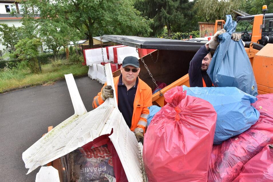 Straßenwärter Holger Zschiedrich (l..) und Jürgen Lindner haben die gefüllten Müllsäcke im Freitaler Stadtgebiet eingesammelt und laden sie am Bauhof ab.