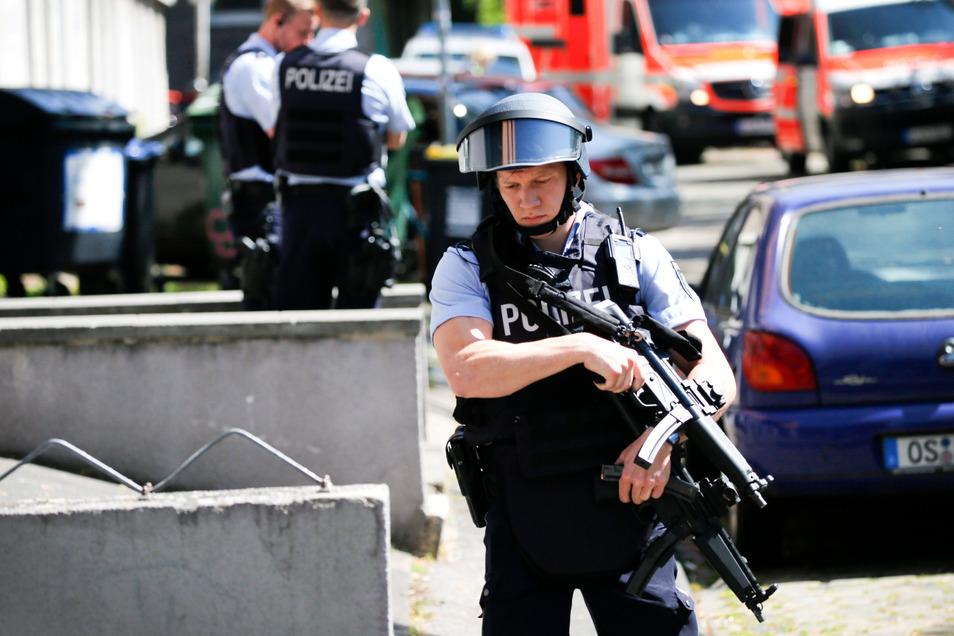 Einsatzkräfte der Polizei stehen vor einem Haus in Köln. Eine Frau soll in einer Kölner Arztpraxis mehrfach mit einer Schreckschusspistole geschossen haben.
