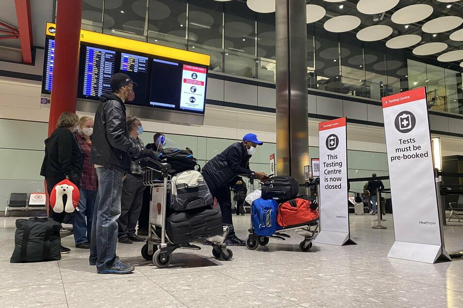 Passagiere warten vor dem Eingang eines Corona-Testzentrums in der Ankunftshalle von Terminal 5 am Londoner Flughafen Heathrow, nachdem sie in Großbritannien angekommen sind.