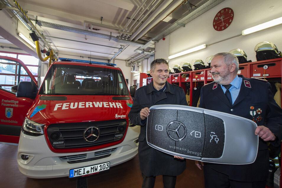 Eckhard Häßler (r.) nimmt im symbolisch von Bürgermeister Siegfried Zenker den Schlüssel für den neuen Mannschaftstransportwagen (MTW) entgegen.
