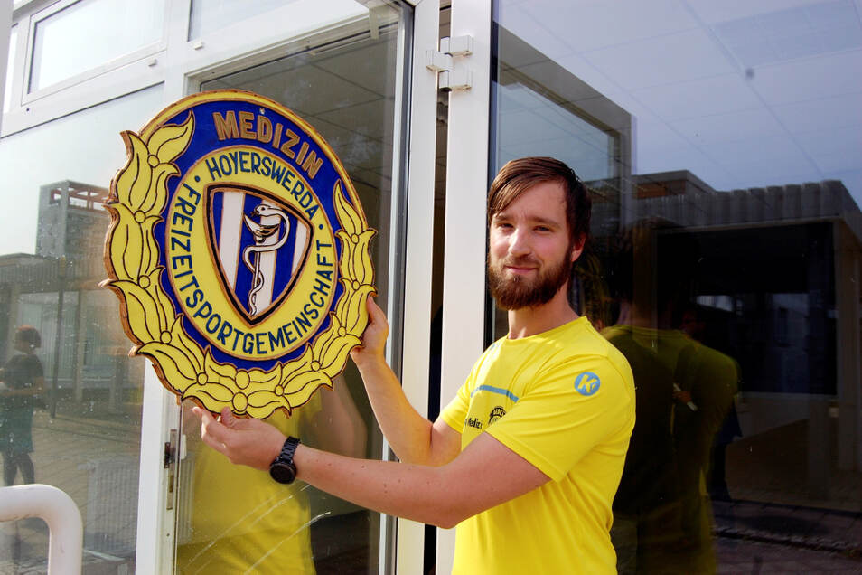 FSG-Übungsleiter Maik Vorback probiert schon mal: Das Logo des Vereins macht sich am Eingang in der Bonhoefferstraße ganz gut.