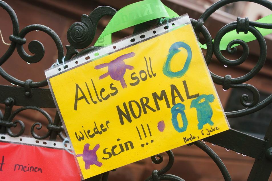"""""""Alles soll wieder normal sein"""" steht als Wunsch auf einem Blatt, das die 6-jährige Mayla zusammen mit Personal aus ihrer Kita und anderen Kindern an das Gitter des Gerechtigkeitsbrunnens vor dem Frankfurter Römer aufgehängt hat."""