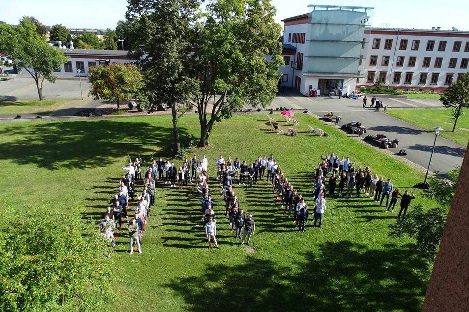 """Der Jahrgang 2021 der Riesaer BA-Studenten bildet auf dem Campus in Gröba den Schriftzug """"Imma""""."""