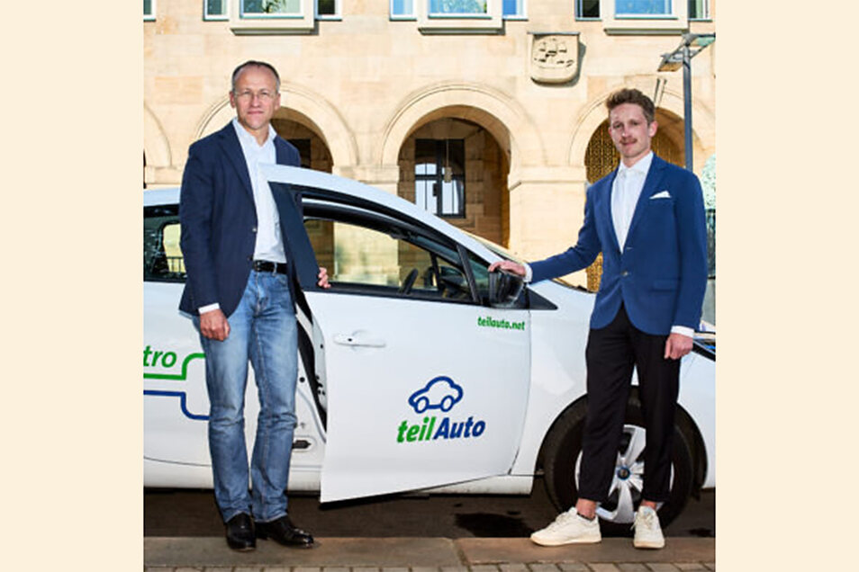 Verwaltungsbürgermeister Dr. Peter Lames und Marcus Buchfeld von Teil-Auto vor einem Carsharing-E-Auto.