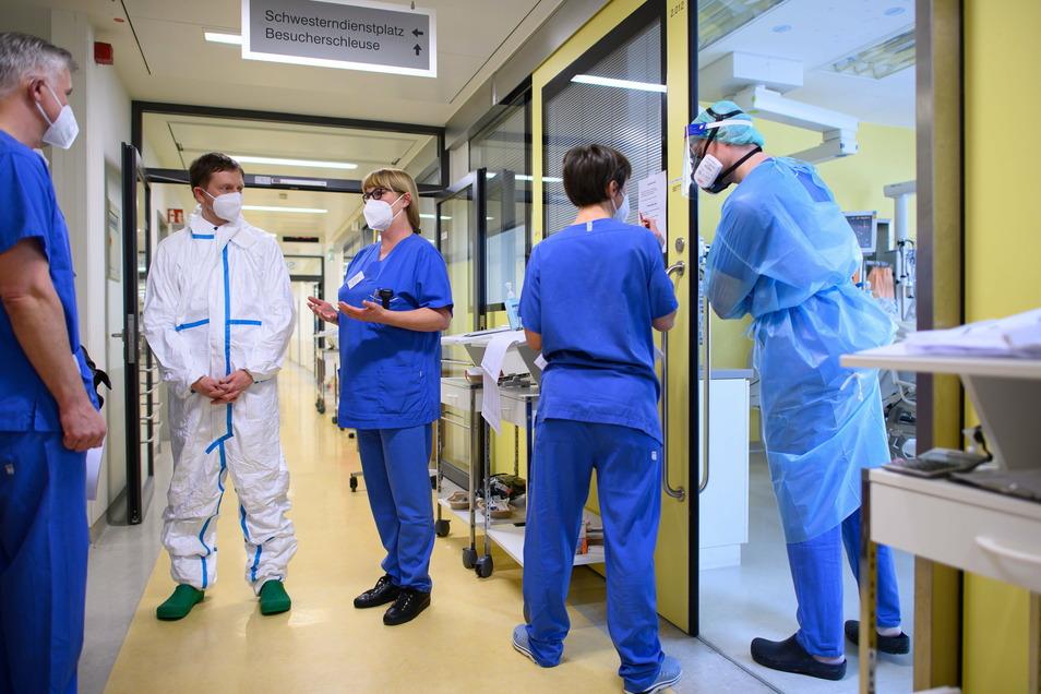 Michael Kretschmer (CDU, 2.v.l.) steht im Vollschutzanzug auf der Covid-19 Intensivstation im Städtischen Klinikum Dresden.