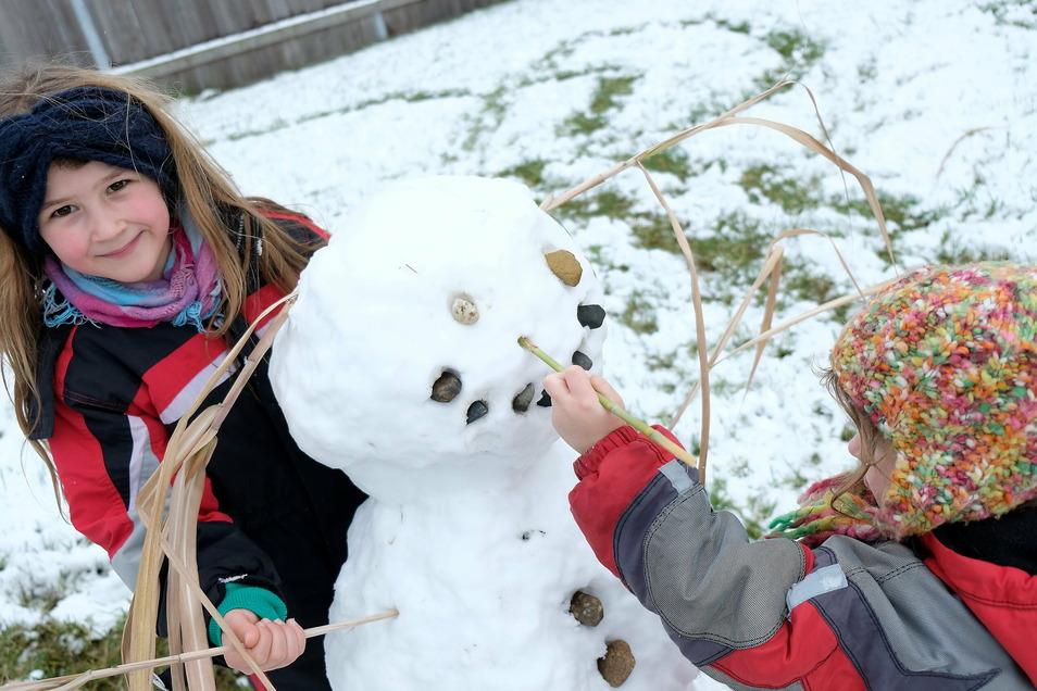Nell und ihre Schwester bauen einen Schneemann.