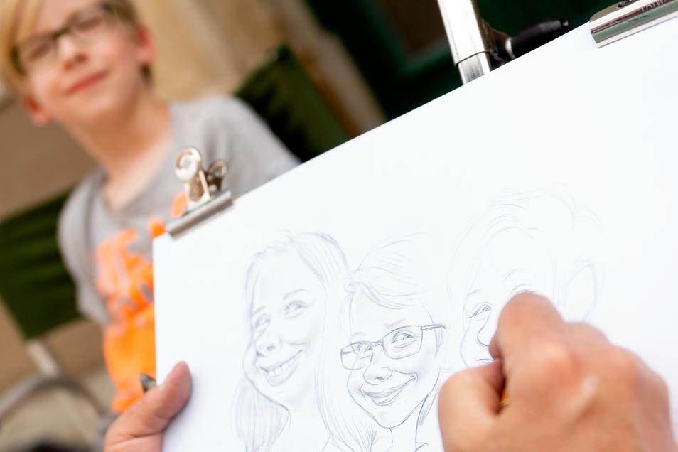 Porträt mit dem Zeichenstift:Viele Stände entlang der Hauptstraße luden zum Bummeln ein. Begehrt war von vielen ein handgezeichnetes Porträt. Dieser junge Festbesucher lässt sich neben zwei Mädchen aufs Papier bringen.