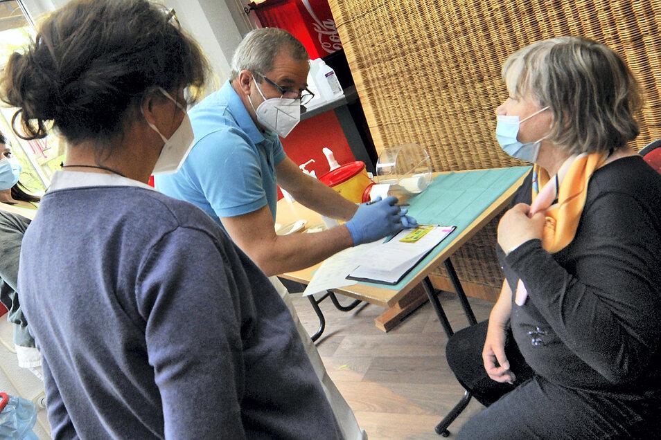 """Unter den ersten von etwa 200 """"Impflingen"""" am Freitag im lokalen Impfzentrum im """"Lindenhof"""" war Heidemarie Jakubik (rechts) aus Bad Muskau. Hausarzt Wladimir Grez (2. v. li,) beantwortete zunächst ihre Fragen, bevor sie den Piks in den Oberarm be"""