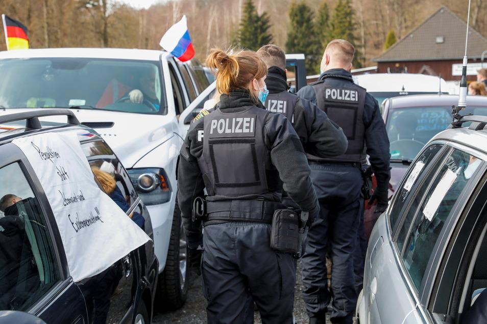 Polizisten achten auf dem Kundgebungsplatz in Großschönau darauf, dass die Fahrer beim Aussteigen eine Mund-Nasen-Maske tragen.