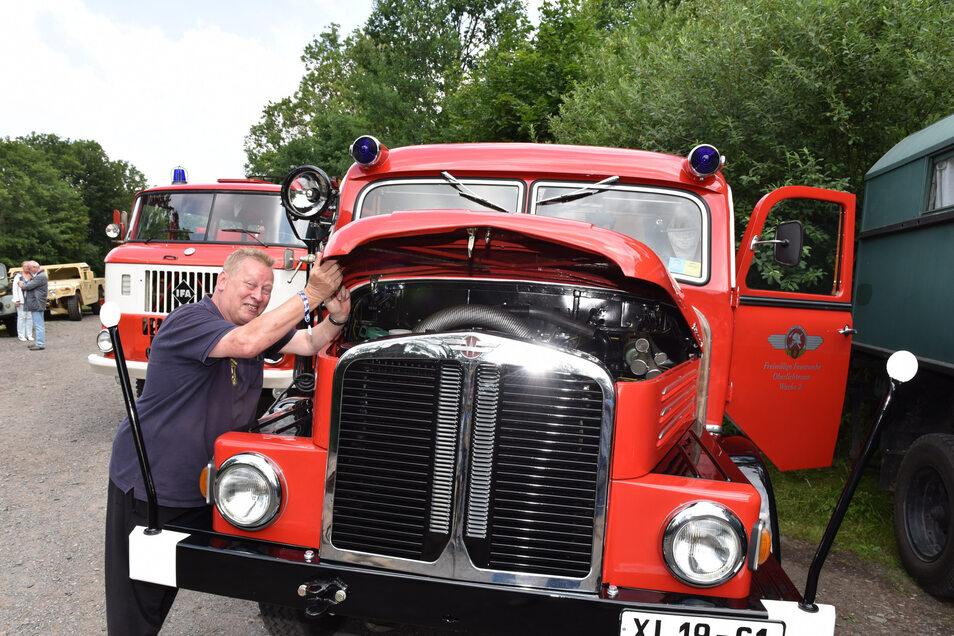 Der Feuerwehrmann Andreas Schneider an einem historischen Einsatzfahrzeug.