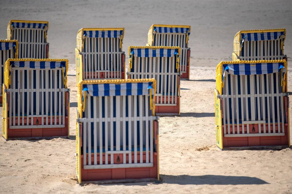 Strandkörbe stehen am kaum besuchten Strand von Cuxhaven. Urlaub an der Küste soll bald wieder möglich sein.
