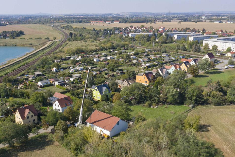 Dort, wo der Mast des Autokrans in die Höhe ragt, soll ein neuer Funkmast entstehen. Der steht dann direkt an der Einfamilienhaus-Siedlung Langenberger Straße in Zeithain. Links sind die Bahnstrecke Dresden-Leipzig und die ard-Kiesgrube zu erkennen.