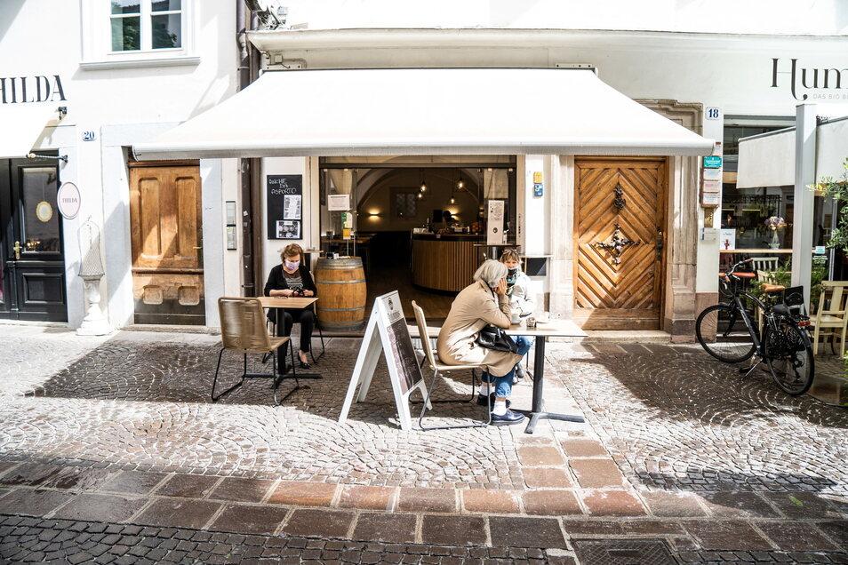 Frauen mit Mundschutz trinken Kaffee vor einer Bar im norditalienischen Bozen.