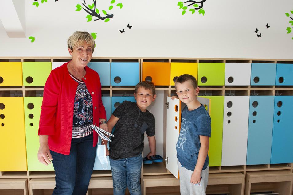 Hortleiterin Romy Potzge, Finn und Robin freuen sich über die freundlich gestalteten Horträume, hier die Garderobe.