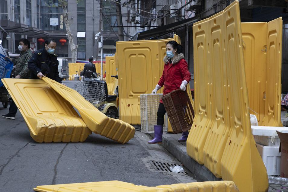 Ein Stadtarbeiter (l) beseitigt Barrieren, die dazu dienten, eine Gemeinde der Stadt Wuhan abzuschotten.