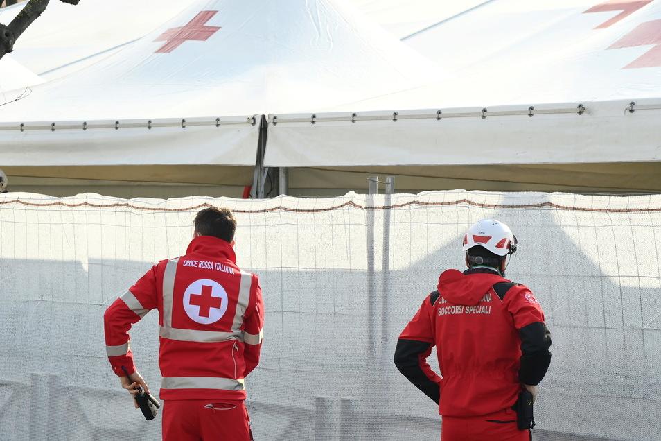 Zwei Mitarbeiter des roten Kreuzes stehen vor einem Zelt, welches für ein Impfstoffzentrum auf der Piazza dei Cinquecento in Rom errichtet wurde.
