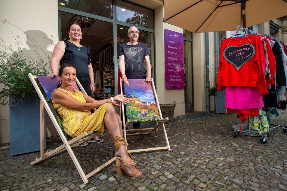 Gudrun und Pia Ast vom gleichnamigen Parfümerie- und Modegeschäft sowie Peter Pförtsch von Janny's Eis (v.l.n.r.) laden Kunden dazu ein, auf den Liegestühlen vor ihren Geschäften an der Bahnhofstraße zu verweilen.