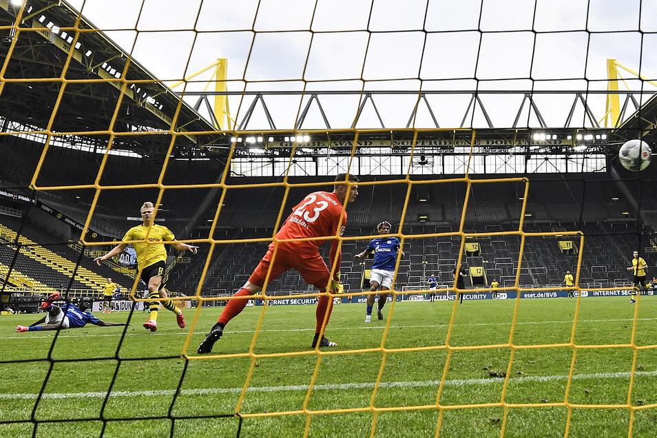 Das 1:0 für Dortmund: Erling Haaland (4. v. l.) erzielt das erste Tor in der Bundesliga nach dem Neustart, Schalke-Torwart Markus Schubert (vorn) ist chancenlos. Foto: dpa/Martin Meissner