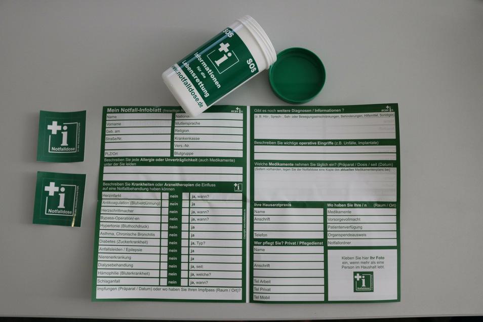 Die Notfalldose mit Inhalt: Notfall-Infoblatt sowie ein Aufkleber für Kühlschranktür und einer für die Innenseite der Eingangstür.
