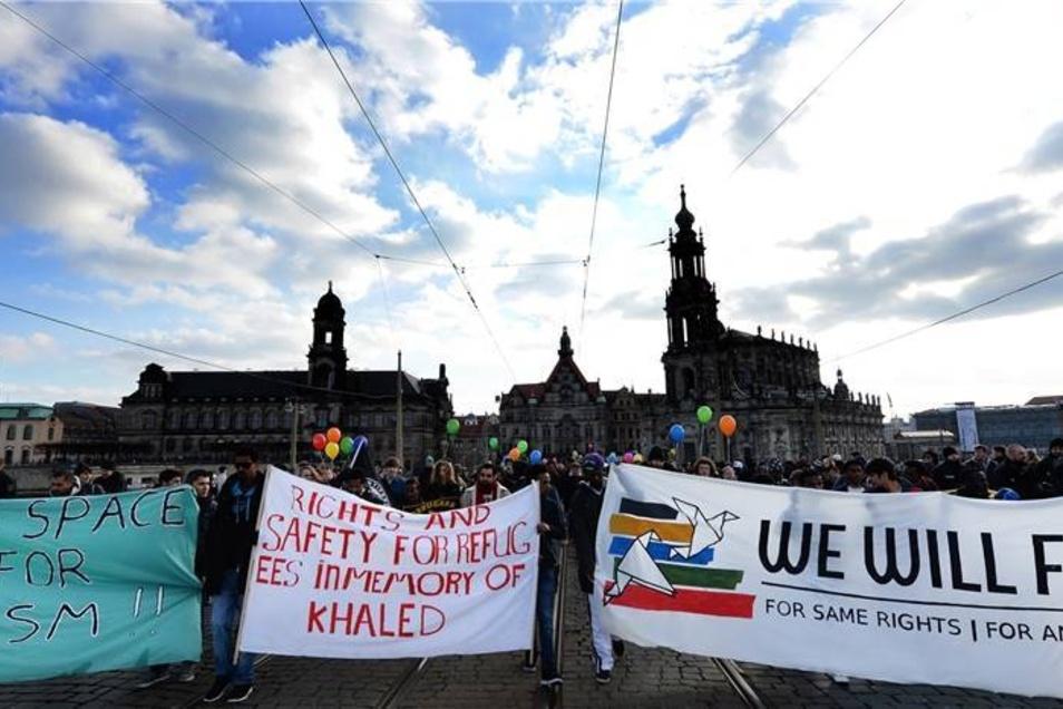 Teilnehmer einer bundesweiten Demonstration für die Interessen von Flüchtlingen laufen am Sonnabend mit Transparenten über die Augustusbrücke in Dresden.