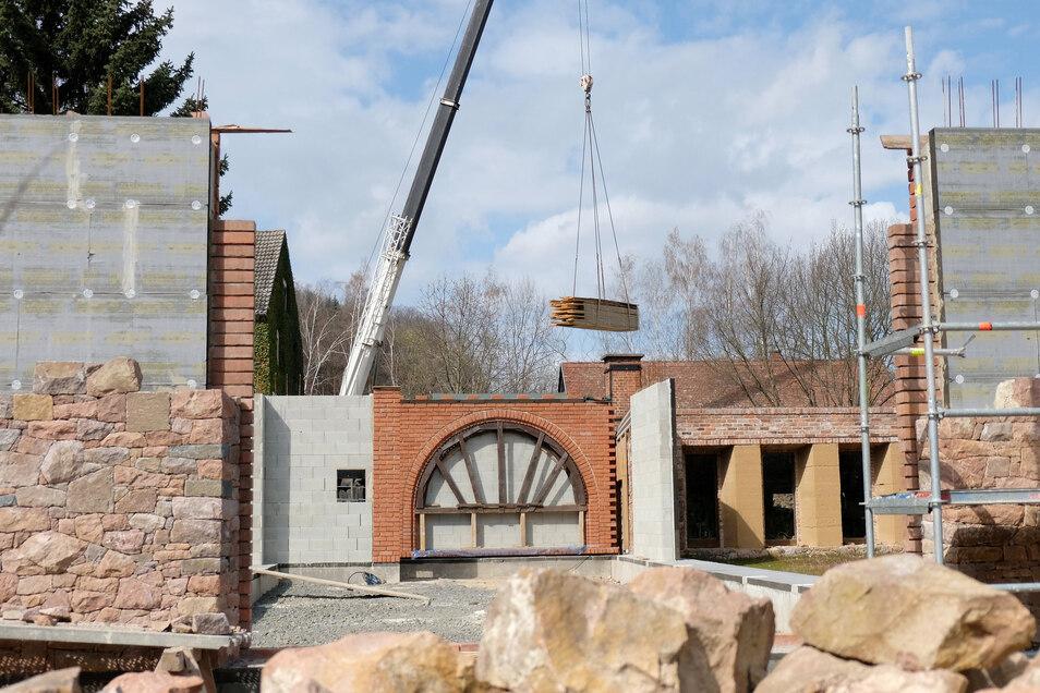 Blick auf die Baustelle des neu entstehenden Veranstaltungsgebäudes auf dem Gelände des Meißner Hahnemannzentrums. Gerade werden Bretter und Dachbalken angeliefert.