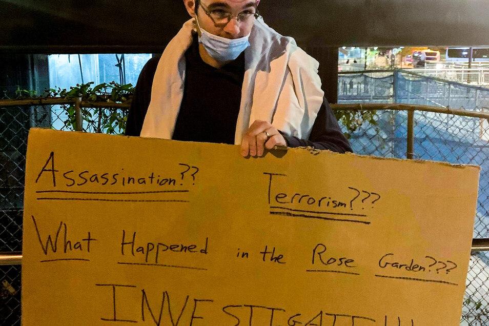 """Trump-Anhänger Will steht mit einem Schild mit der Aufschrift """"Attentat?? Terrorismus??? Was passierte im Rosengarten??? Ermittelt!!!"""" vor der Klinik."""