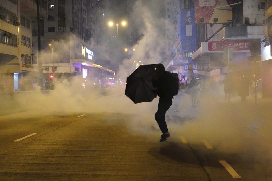 Ein regierungskritischer Demonstrant schützt sich in Hongkong mit einem Regenschirm vor Tränengas.