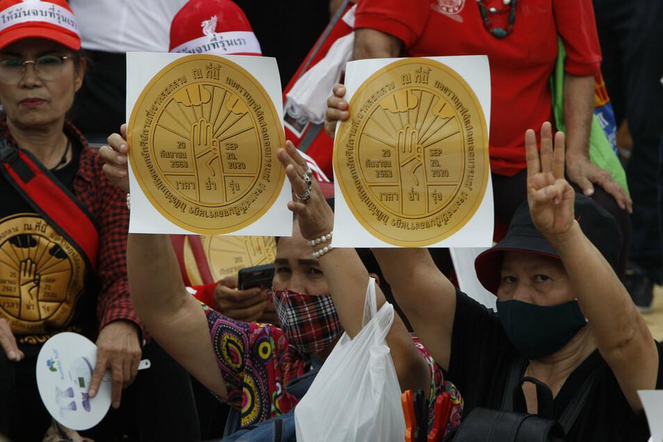 Demonstranten halten vor dem Parlament Plakate, auf denen eine Plakette mit der Inschrift «Dieses Land gehört dem Volk und nicht dem Monarchen.» aufgebildet ist.
