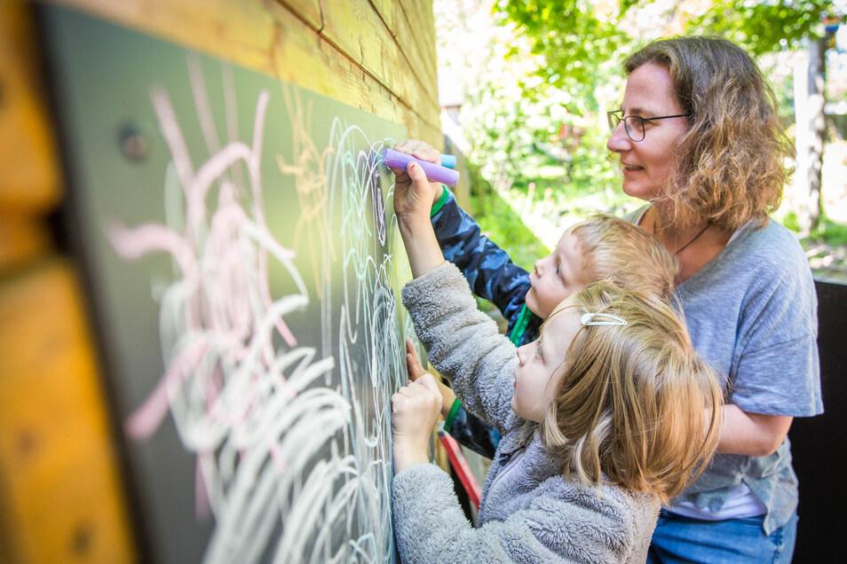 Gerade wurden in der Kita Regenbogen Außenmaltafeln angebracht. Erzieherin Anja Kaps malt mit August und Magdalena.