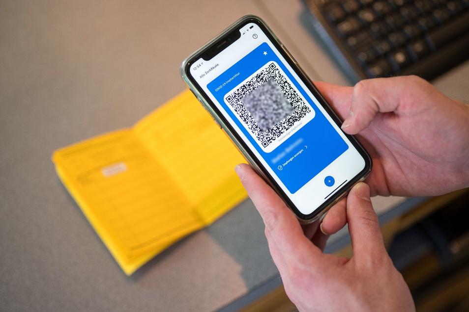 Ein Smartphone zeigt den QR Code eines digitalen Impfausweises, während auf dem Tisch Impfbuch liegt.
