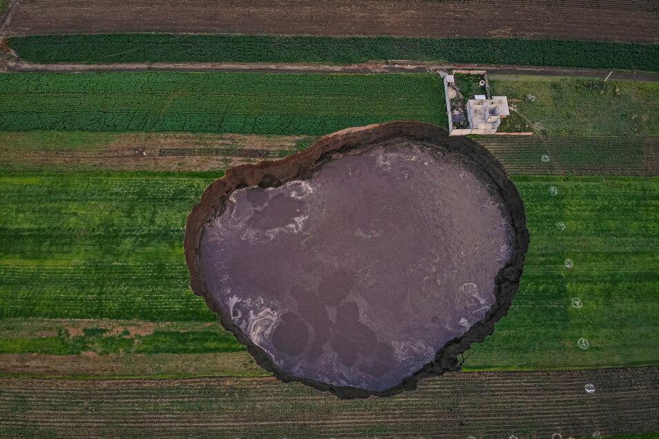 Aus der Vogelperspektive ist der große mit Wasser gefüllter Krater zu sehen.