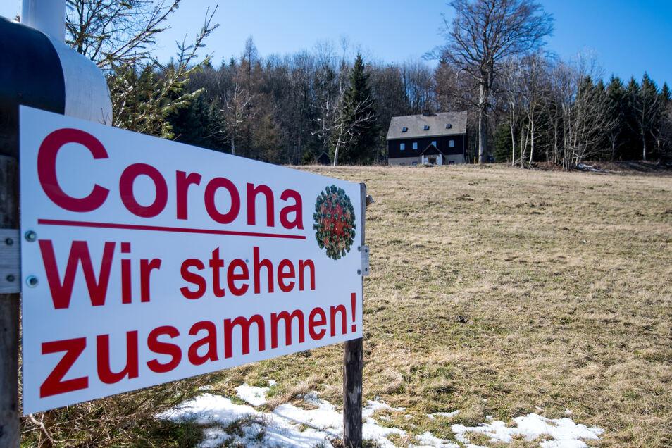 """Am Ortseingang Bärenstein im Erzgebirge verkündet ein Schild """"Corona - Wir stehen zusammen!"""". Bärenstein und der tschechische Ort Vejprty teilen sich ein gemeinsames Zentrum."""