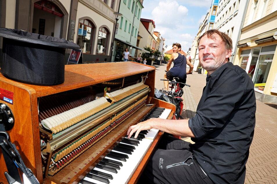 Strampelnd und spielend über die Riesaer Hauptstraße: Andreas Güstel (am Klavier) und Julian Eilenberger (auf dem Fahrrad)