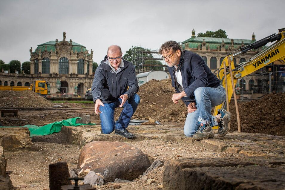 Gesteinsexperte Jan-Michael Lange (l.) und Archäologe Hartmut Olbrich inspizieren den Findling mit der kyrillischen Schrift im Zwingerhof. Zum Auftakt der Grabungen wurde hier viel entdeckt.