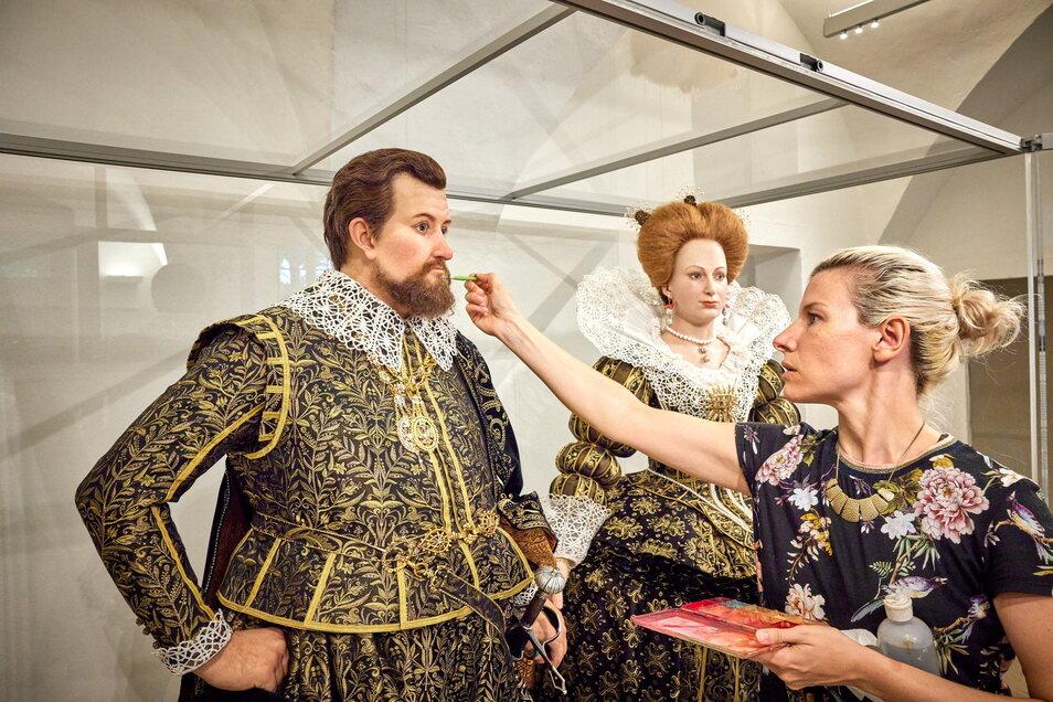 Letzte Pinselstriche, bevor die Figuren hinter Glas kommen: Maskenbildnerin Lisa Büscher richtet den Bart von Kurfürst Johann Georg I. von Sachsen.