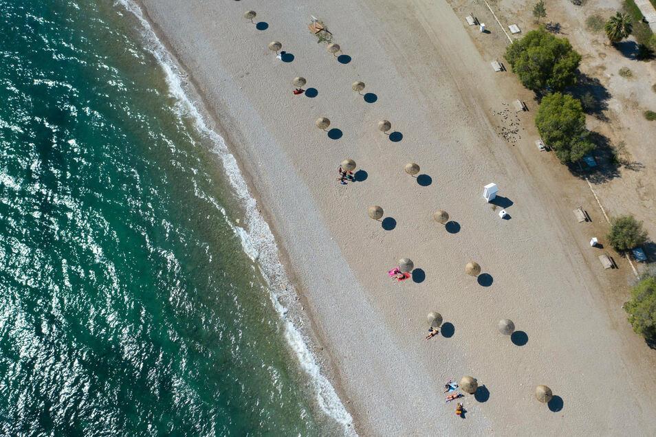 Den Abstand einhalten? Kein Problem: An Strand südlich von Athen stehen Sonnenschirme für Strandbesucher bereit.