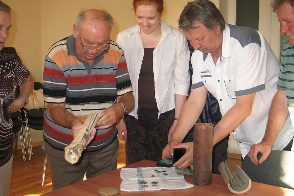 Erwartungsvoll schauen Rudolf Krahl vom Gemeindekirchenrat, Pfarrerin Miriam Arndt und Bürgermeister Dieter Noack (v.li.) auf das, was aus der Schatulle alles zum Vorschein kommt.