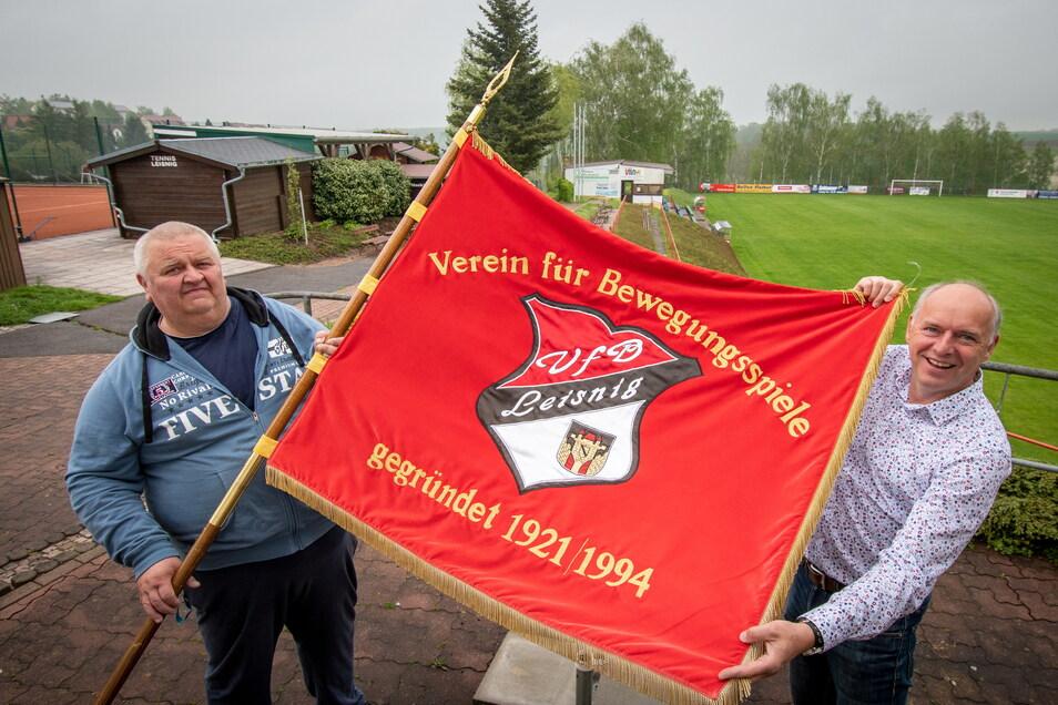 Vereinsmitglied Frank Günther und VfB-Präsident Jörg Lippert (rechts) sind stolz auf die Vereinsfahne. Auch sie zeigt, dass in diesem Jahr ein besonders Jubiläum ansteht, der VfB auf den 100. Jahrestag der Gründung verweisen kann – der Erstgründun