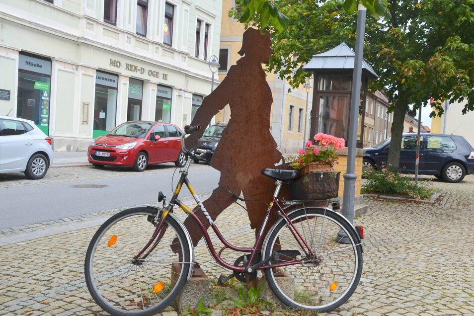 Bunte Tupfen: Eines der beiden mit Blumenkörben bestückten Fahrräder auf dem Marktplatz Reichenbach. Die ehemaligen Geschäfte der Häuser im Hintergrund stehen seit langer Zeit leer.