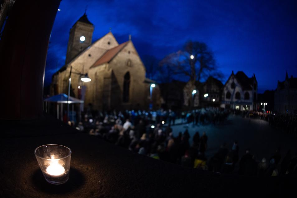 Besucher stehen beim ökumenischen Gottesdienst an der Kirche St. Marien, während eine Kerze auf der Rathaustreppe brennt.