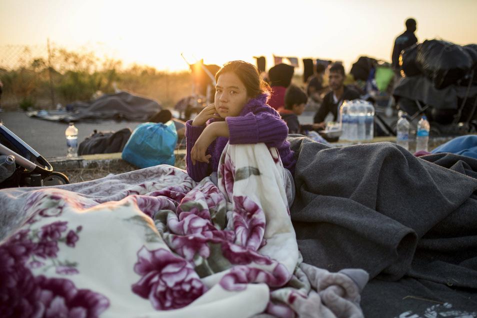 Eine junge Frau sitzt am Rande einer Straße unweit des ausgebrannten Flüchtlingslagers Moria.