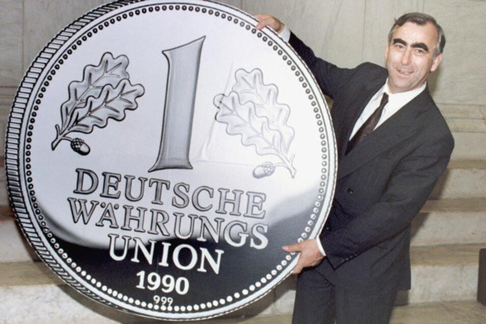 So groß ist die D-Mark: Bundesfinanzminister Theo Waigel mit übergroßer Gedenkmünze kurz vor der Währungsunion Ende Juni 1990 in Ost-Berlin.