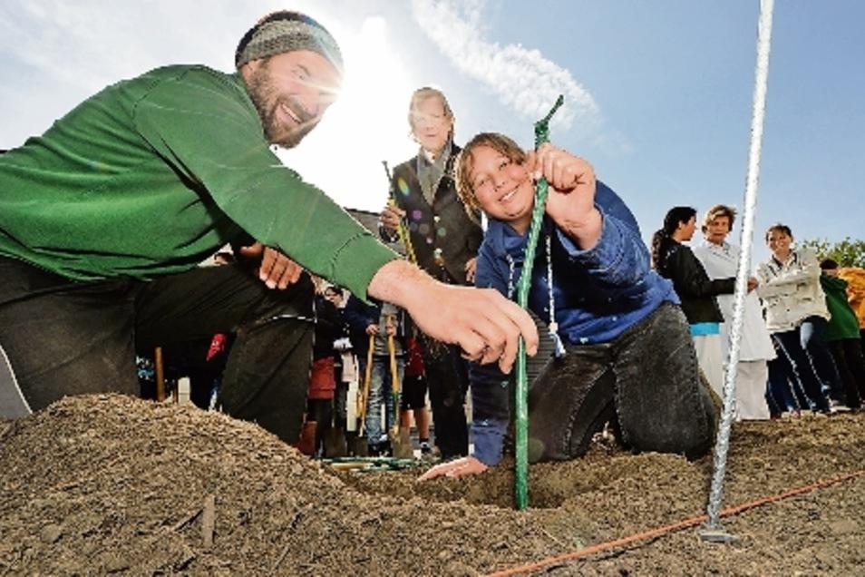 So wird eine Solaris-Rebe gepflanzt. Weinbaumeister Till Neumeister (l.), erklaert Annalena (r.) aus der 6. Klasse der OS Mitte in Radebeul, wie das gemacht wird.