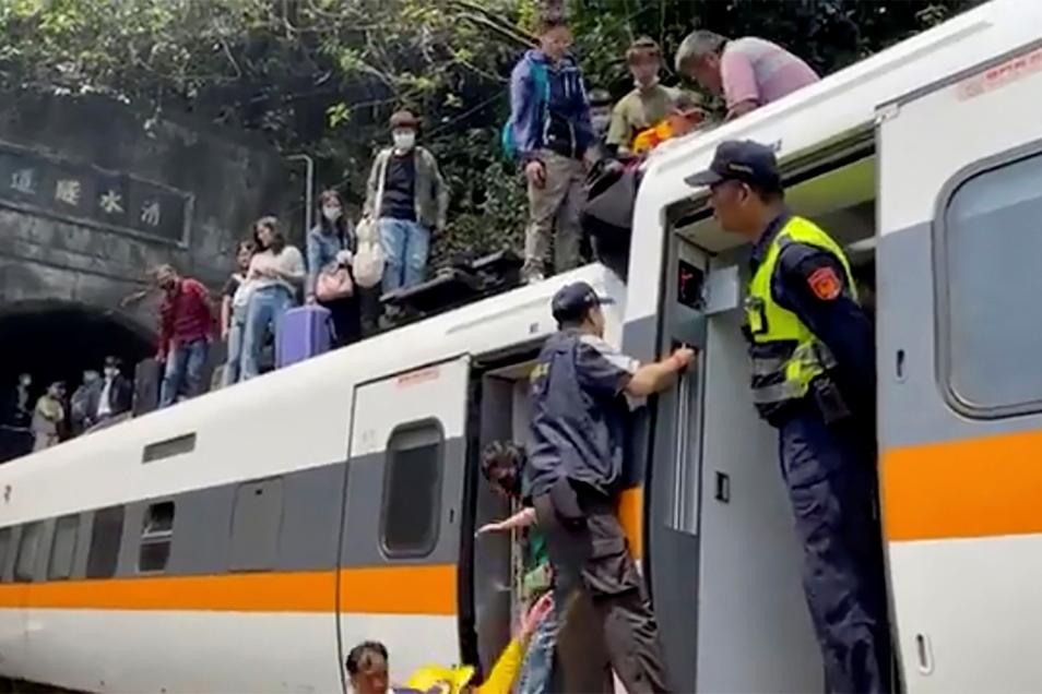 Passagieren wird geholfen, aus einem entgleisten Zug zu klettern.