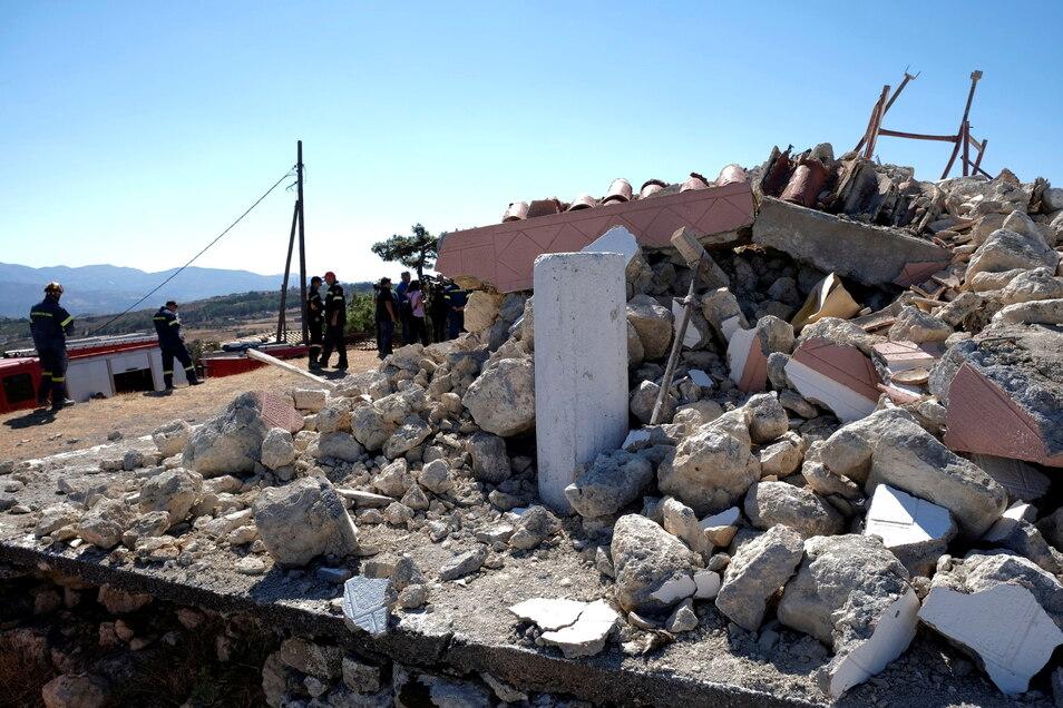 Feuerwehrleute stehen neben der zerstörten Kirche Profitis Ilias.