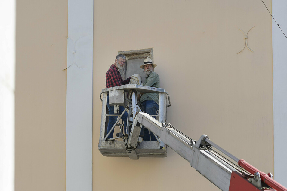 Hans (links) und Michael Herbig von der Firma Herbig Denkmalpflege aus Ostritz bringen den aus Sandstein gefertigten Mönchskopf in der Fensternische an.