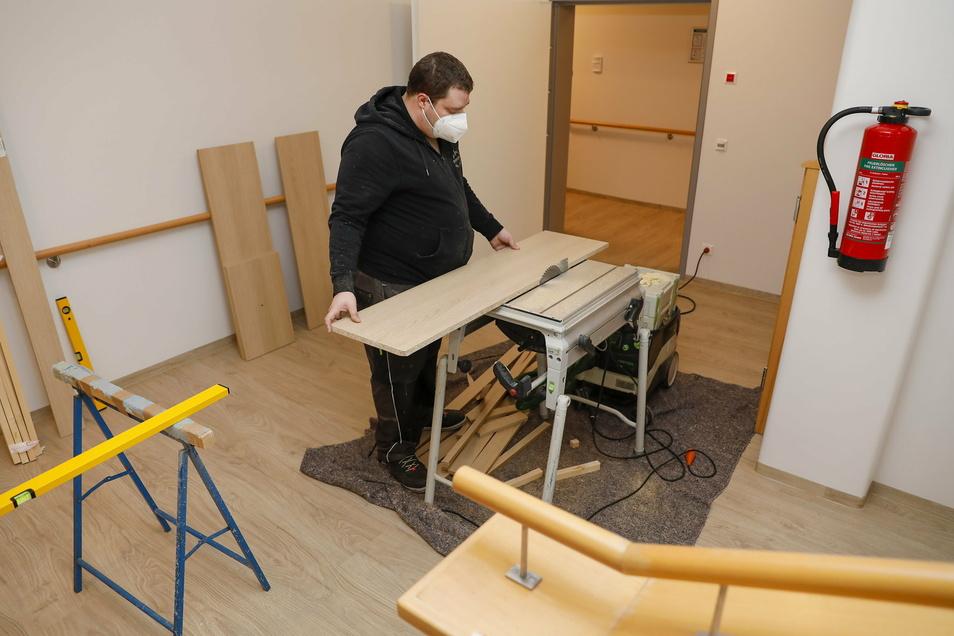 Im Neubau werden noch in einigen Zimmern die Einbaumöbel aufgebaut. Alexander Schneider sägt hier gerade ein Brett für einen Schrank zurecht.