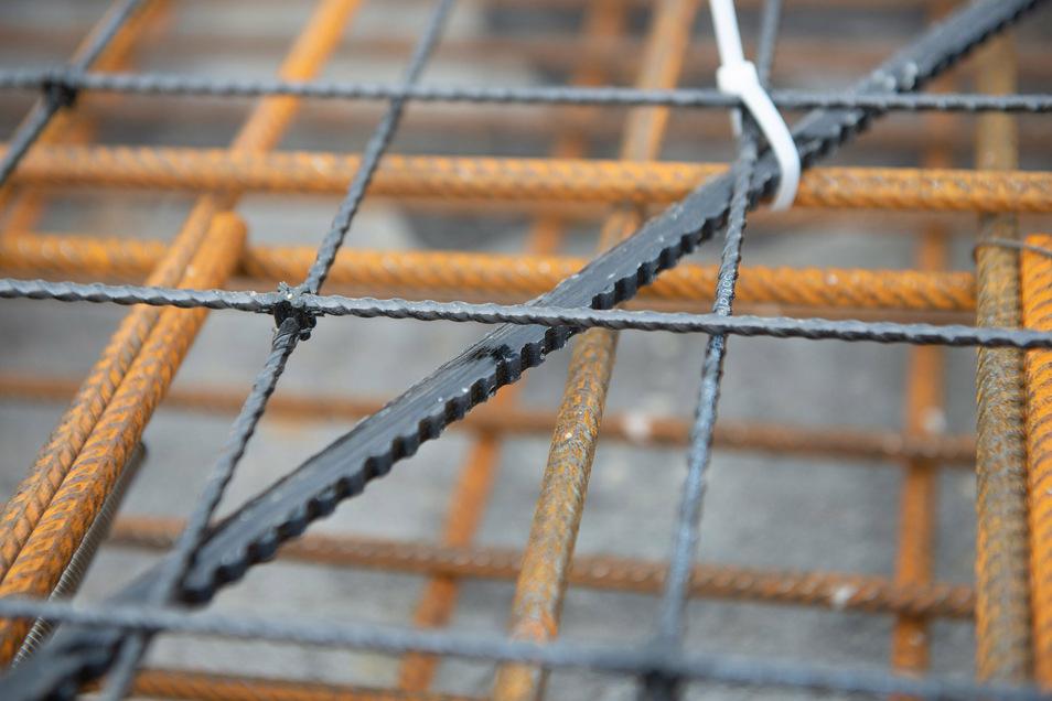 Ein Blick ins Geflecht der Bewehrung. Unten sind die Stahlstäbe sichtbar, dann ein Basaltstab als Abstandshalter und darüber die Carbonmatte.