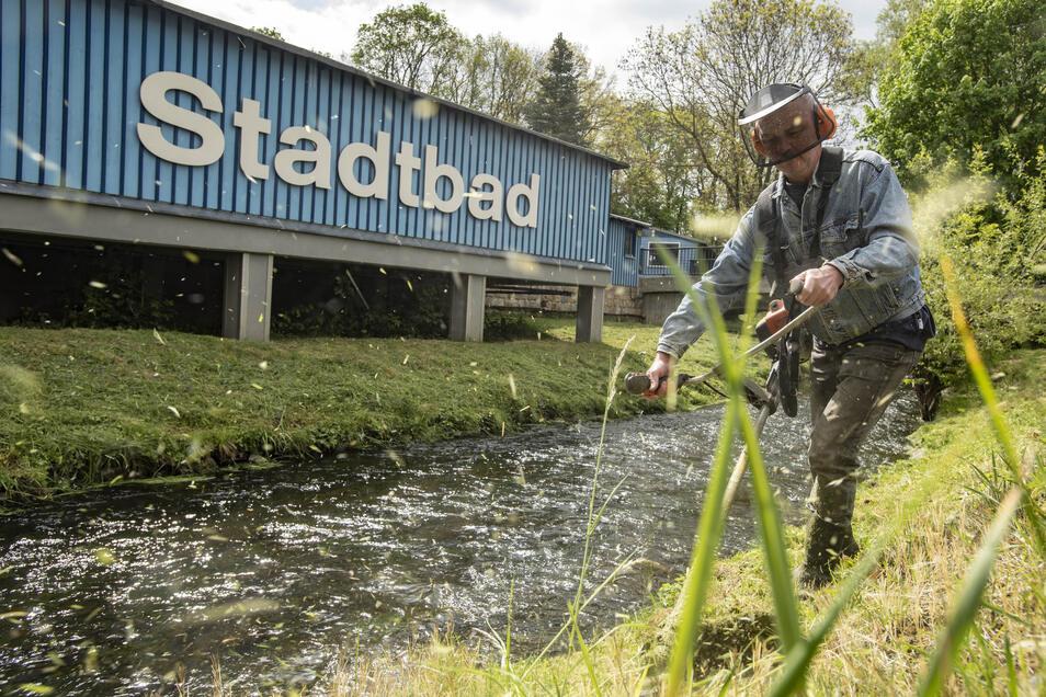 Auch vor dem Stadtbad wird eifrig gewerkelt. Mitarbeiter Bernd Hesse schneidet das Gras des Hanges zur Röder kurz.